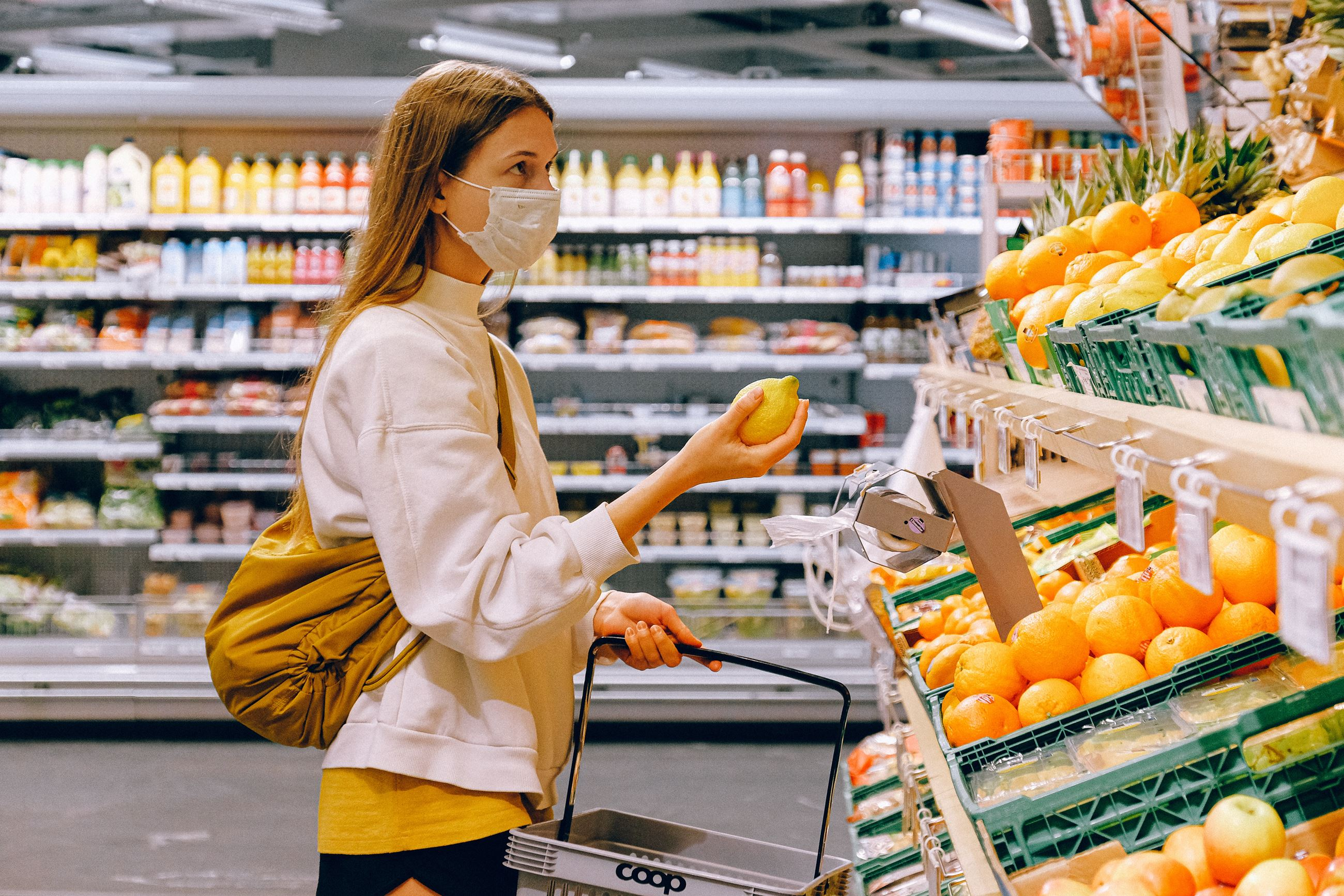 woman-in-yellow-tshirt-and-beige-jacket-holding-a-fruit-3962285