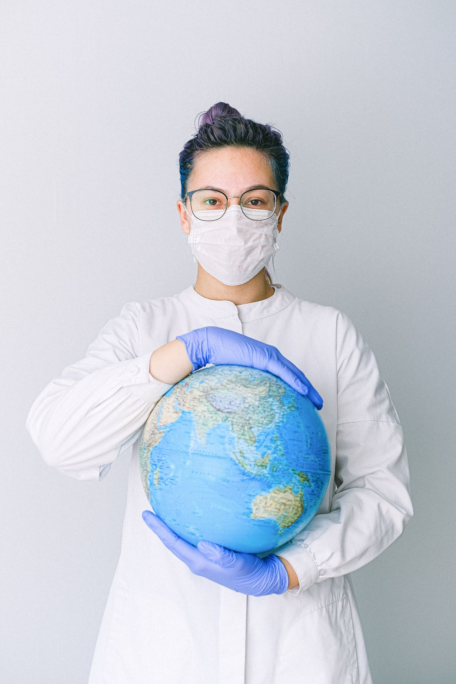 person-with-a-face-mask-and-latex-gloves-holding-a-globe-4167542